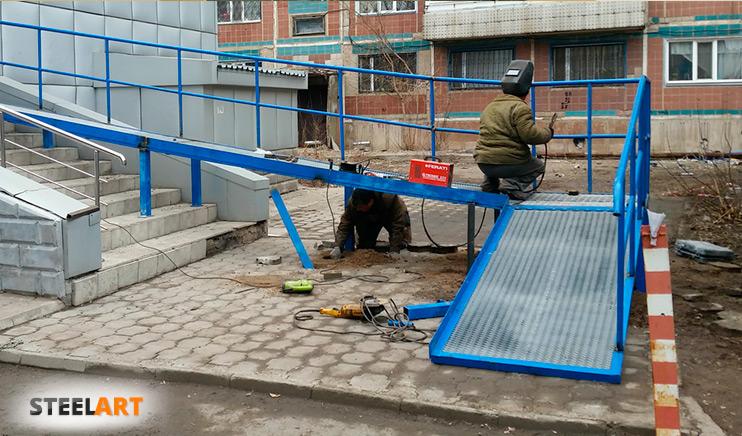 Монтажники устанавливают стационарный пандус из нержавейки