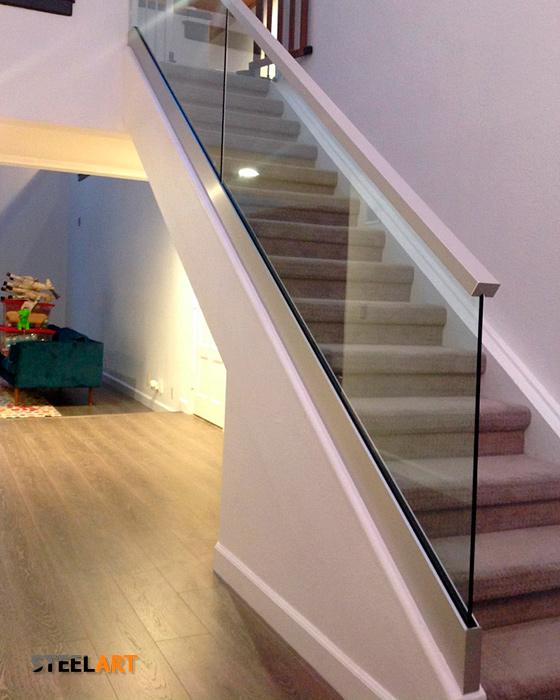 Стеклянные перила на лестнице с накладным поручнем