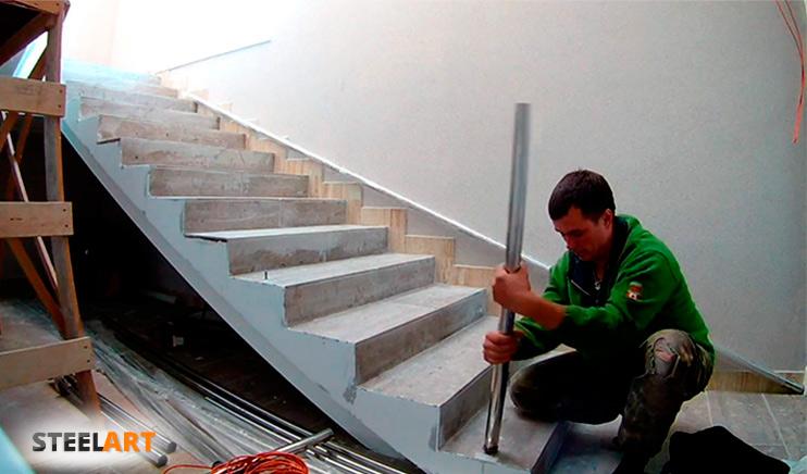 Монтаж перил их нержавеющей стали на лестнице монтажником